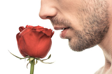 Young man smelling a rose